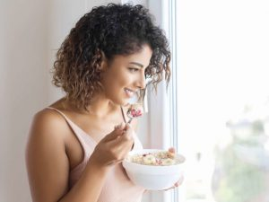 A woman eating a food at window